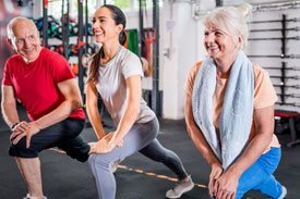 Personal trainer with senior couple doing rehab exercises at the gym
