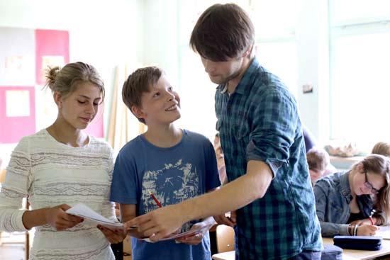 Lehrer redet mit zwei Schüler*n