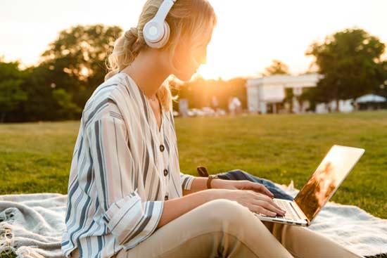 Studentin auf einer Wiese am Laptop