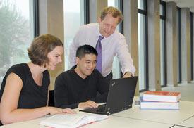 Zwei Studierende bekommen von einem Dozenten auf dem Laptopbildschirm etwas gezeigt