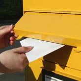 Brief wird in Briefkasten gesteckt