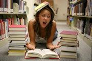 Mädchen liegt in Bib auf dem Boden mit Bücherstapeln um sich und Buch auf dem Kopf