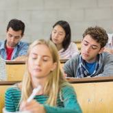 StudentInnen sitzen im Hörsaal und schreiben (eine Klausur)