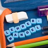 """Schulmäppchen mit Stiften, Radiergummi und """"Lehrermangel"""" aus Buchstabenblöcken"""