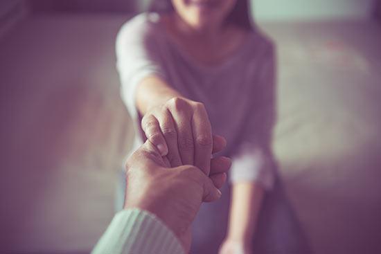 Psychologe reicht einer Patientin die Hand