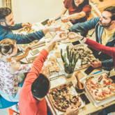 Studentinnen und Studenten essen gemeinsam Pizza in der WG-Küche