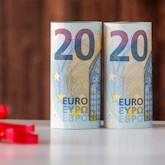 Zwei 20er-Euroscheine so gerollt und aufgestellt, dass 2020 zu lesen ist.
