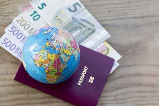 Pass, Globus und Geld auf einer hübschen Holzlatte als Hintergrund