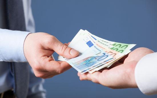 Eine Hand legt Geldscheine in eine andere Hand.
