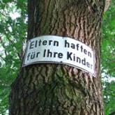 """""""Eltern haften für Ihre Kinder""""-Schild an Baum"""