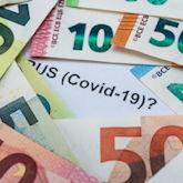 """Viele Geldscheine übereinander gelegt, in der Mitte bleibt vom darunterlegenden Papier """"Covid-19?"""" lesbar"""