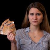 Junge Frau mit Geldscheinen in der Hand und verängstigtem Blick