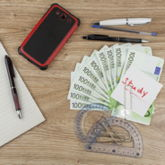 """10 Hundert-Euro-Scheine, Block mit Kugelschreiber, Handy und Büroklammern mit Notiz """"Study"""" auf Holzplatte"""
