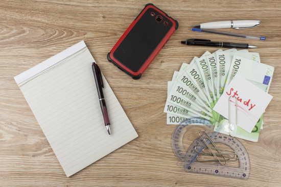 """Kosten des Studiums kalkulieren: 10 Hundert-Euro-Scheine, Block mit Kugelschreiber, Handy und Büroklammern mit Notiz """"Study"""" auf Holzplatte"""