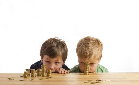Zwei Kinder haben Geldstücke aufgestapelt und ducken sich hinter dem Tisch