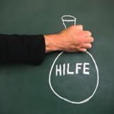 """Sack mit Aufschrift """"Hilfe"""" mit Kreide auf Tafel, gehalten von einer Hand"""
