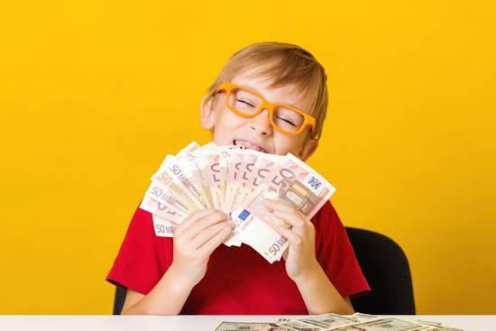 Kind mit Brille hält ein Dutzend 50 Euro-Scheine in den Händen