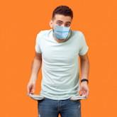 Junger Mann mit enttäuschtem Blick, Mundschutz und leeren Hosentaschen