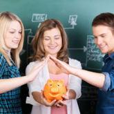 Schülerin hält Sparschwein, umrahmt von zwei Schülern und vor beschriebener Tafel