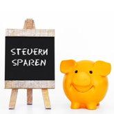 """Gelbes Sparschwein neben kleiner Tafel mit Aufschrift """"STEUERN SPAREN"""""""