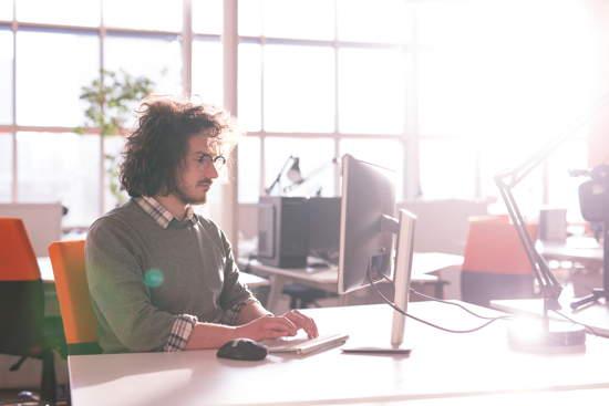 Junger Erwachsener beim Arbeiten in einem Startup