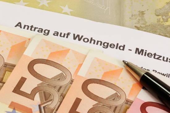 Geldscheine hinter Wohngeldantrag liegend, daneben ein Kugelschreiben