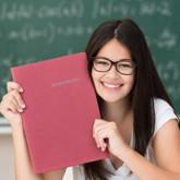 Schülerin mit Bewerbungsmappe, im Hintergrund beschriebene Schultafel