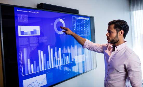 Geschäftsmann analysiert Daten auf einem großen Touchscreen