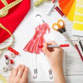 Skizze eines Kleides, umgeben von Stoffschere, Maßband, Farbpalette auf Smartphone