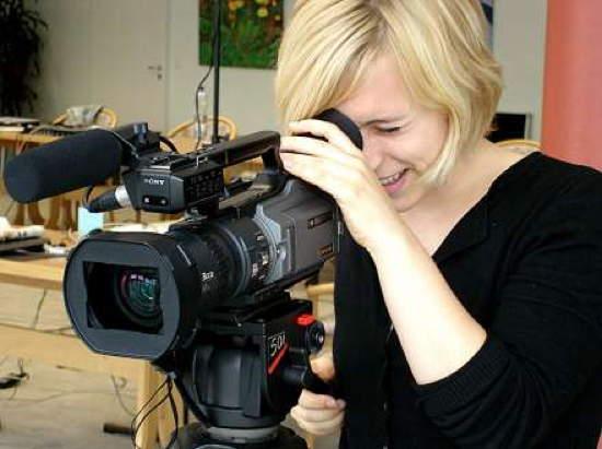 Frau bedient professionelle Videokamera