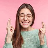 Studentin mit geschlossenen Augen kreuzt die Finger