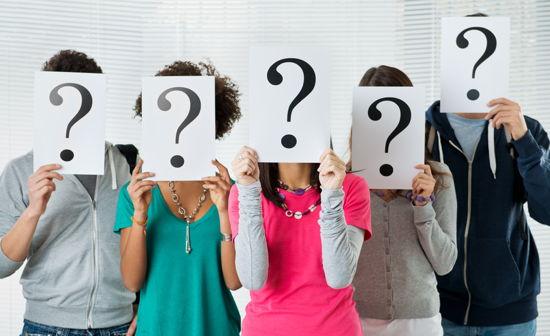 Studierende halten Blätter mit Fragezeichen vor ihre Gesichter