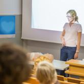 Frau spricht vor Publikum in Hörsaal - vor ihr liegt ein Dummy mit Defibrilator