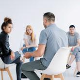 Sozialarbeiter sitzt mit Jugendlichen im Stuhlkreis und redet mit einer Jugendlichen