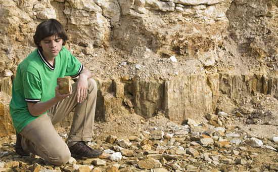 Ein junger Geologe studiert einen Stein