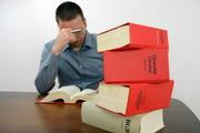 Student, der konzentriert ein Gesetzbuch liest, im Vordergrund weitere dicke Gesetzesbücher übereinandergestapelt
