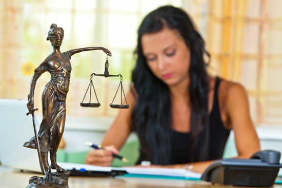 Justitia auf Schreibtisch, im Hintergrund Rechtsanwältin