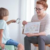 Lehrerin hält eine Zeichnung mit einem Haus, die sie einem Kind zeigt, das eine Lupe in der Hand hält