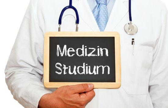 """Person in weißem Kittel und mit Stethoskop hält kleine Tafel """"Medizin Studium"""" in der Hand"""