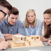 Fünf Studierende schauen sich einen Modellbau eines Hausentwurfes an.