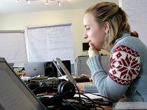 Studentin sitzt an einem Schreibtisch, der vollgestellt mit Laptops, Kopfhörern, Lautsprecherboxen und unterlagen ist. Im Hintergrund stehen Flipcharts