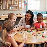 Grundschul-Kinder sitzen mit einer Sozialpädagogin um einen Tisch herum und spielen