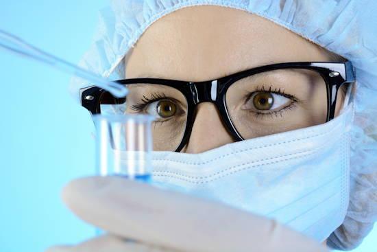 Biomedizinerin schaut Inhalt eines Reagenzglases an