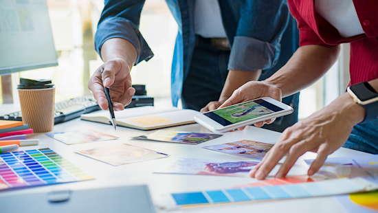 Zwei Personen in einer Designagentur diskutieren Ideen mit Hilfe von Farbpaletten und Fotos
