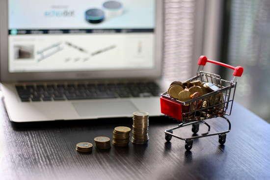 Laptop mit Charts, davor Stapel von Kleingeldmünzen und ein Mini-Einkaufswagen gefüllt mit Geldmünzen