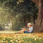 Ein Junge liest unter einer Linde sitzend ein Buch