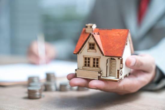 Hand hält Modell von einem kleinem Einfamilienhaus, im Hintergrund sind unscharf Münzgeld und eine Hand, die auf einem Papier etwas schreibt, zu erkennen