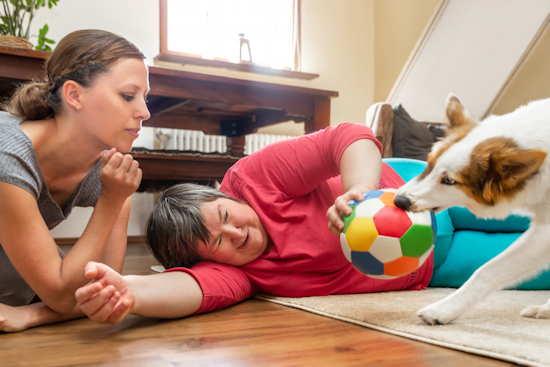 Geistig behinderte Frau spielt betreut mit einem Hund