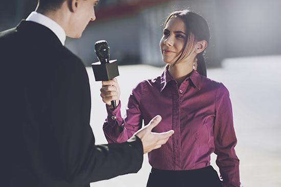Journalistin mit Mikrofon in der Hand erhält Antwort von einem Mann in Anzug