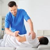 Ein Physiotherapeut arbeitet mit einem Patienten in einer Praxis